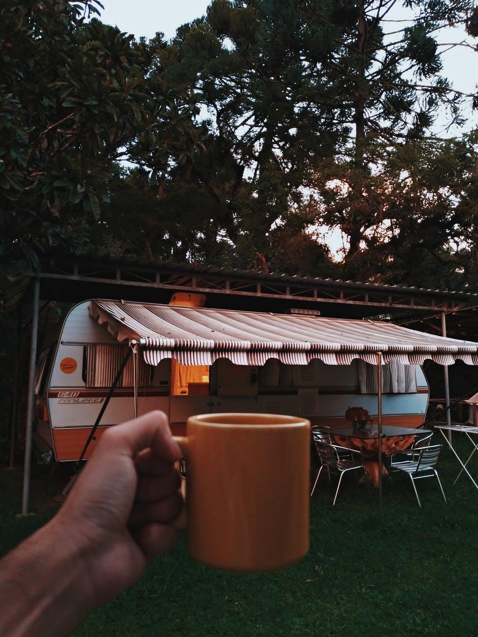 person holding orange mug